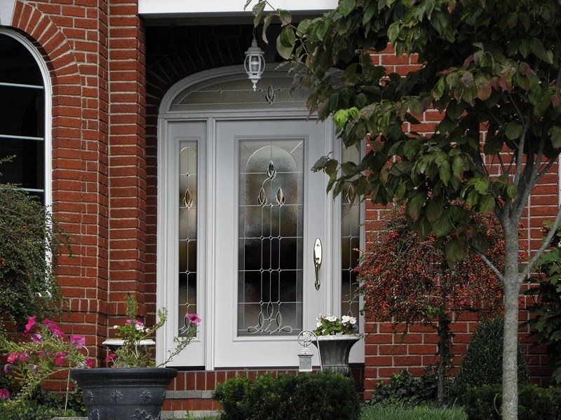 A white front door with frosted main and side glass panels
